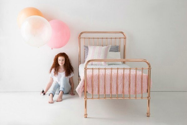 Children's furniture online. Tween sitting next to bed.