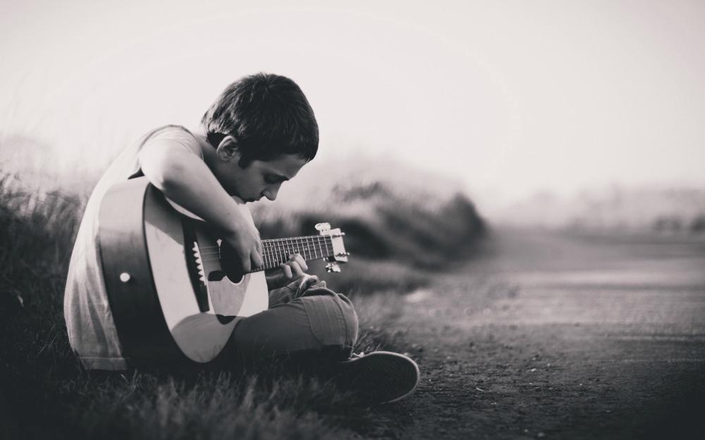 Teenage bullying: Little boy playing guitar, sad.