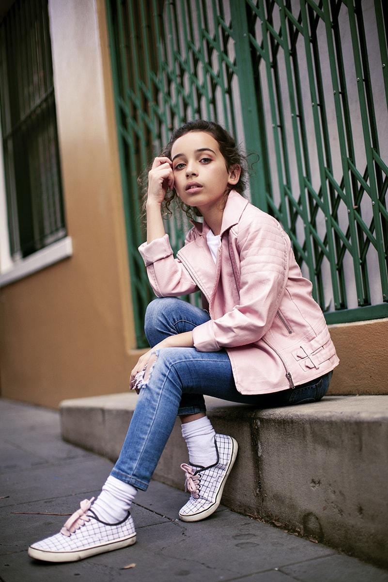 Tween girl wearing pink jacket in fashion shoot