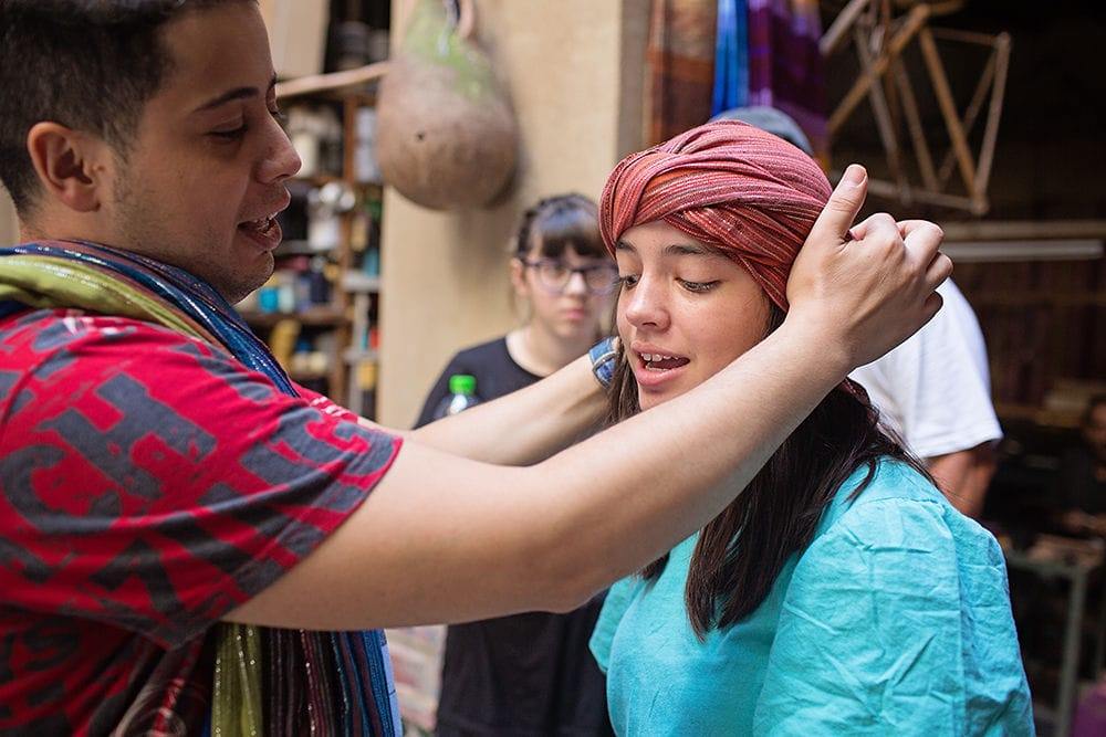 man wrapping turban around girls head