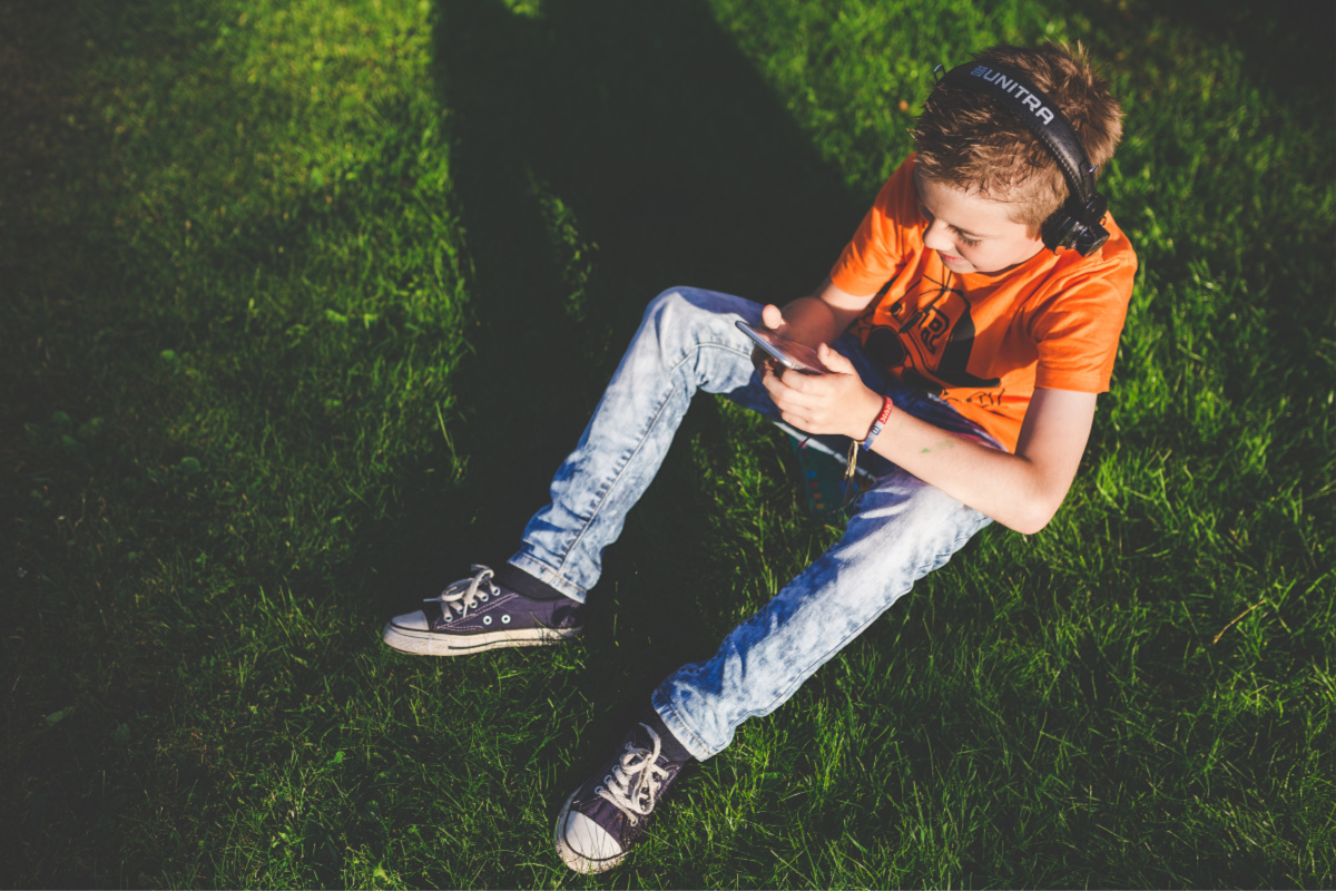 mobile phone safety for kids - tween sitting on grass with mobile phone.