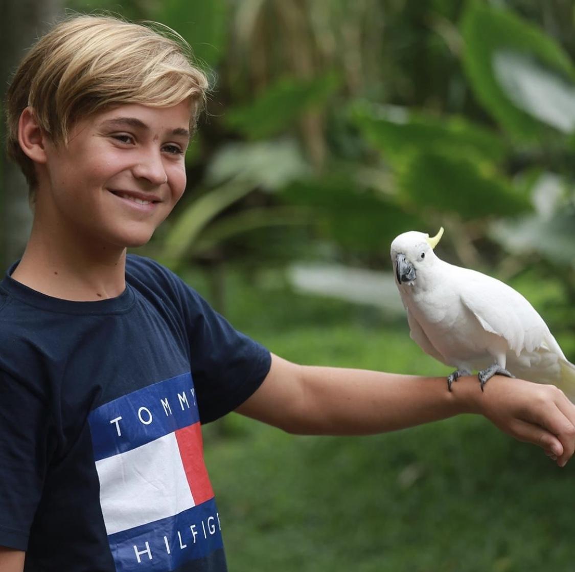 tween boy holding a cockatoo