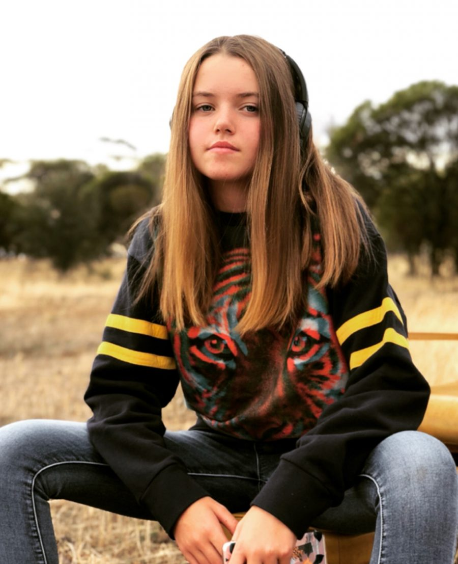 Young girl sitting on a stool in a paddock. Long Distance Parent Relationship - Boarding School