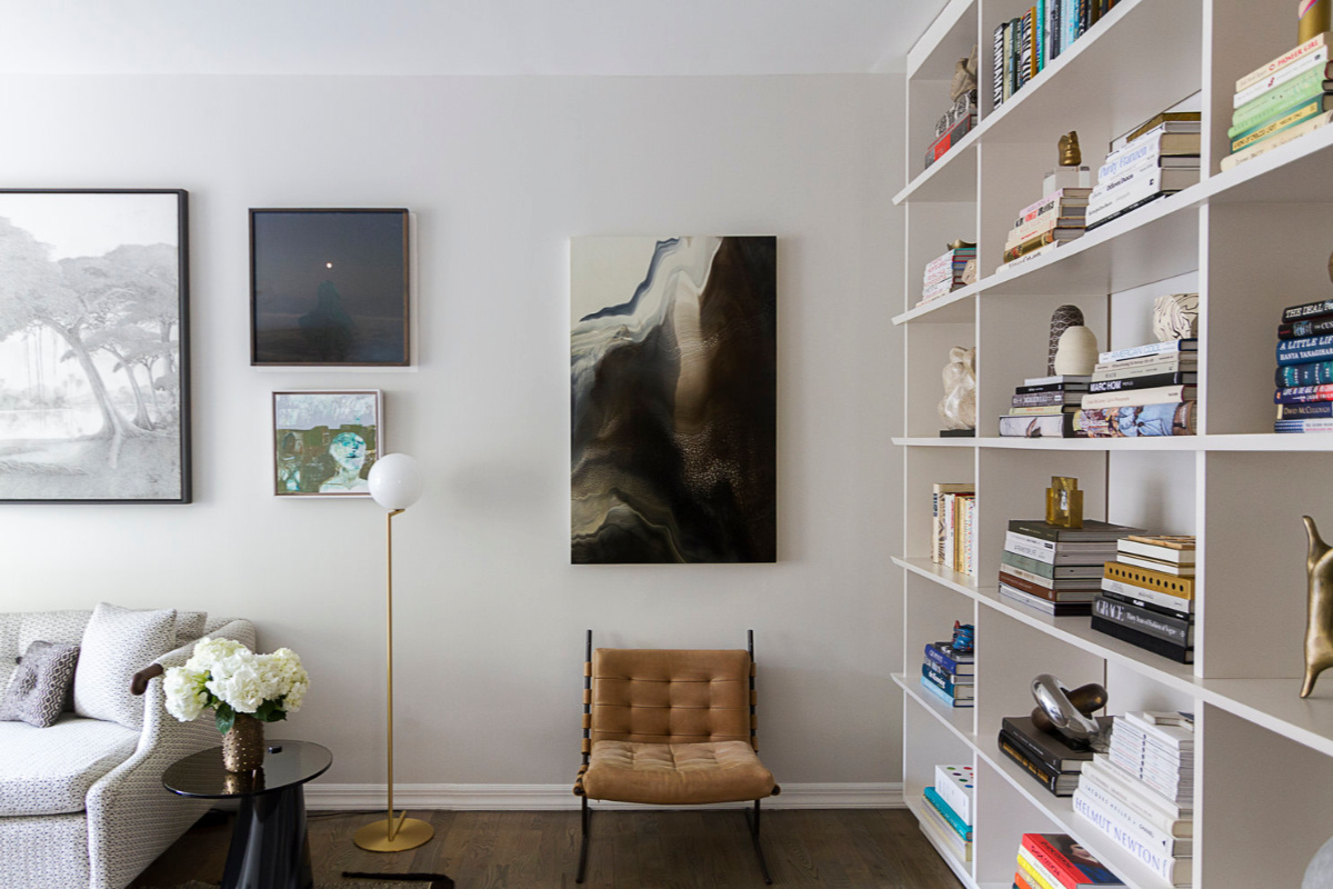 Living room with modern decor - lounge, book case and wall art.
