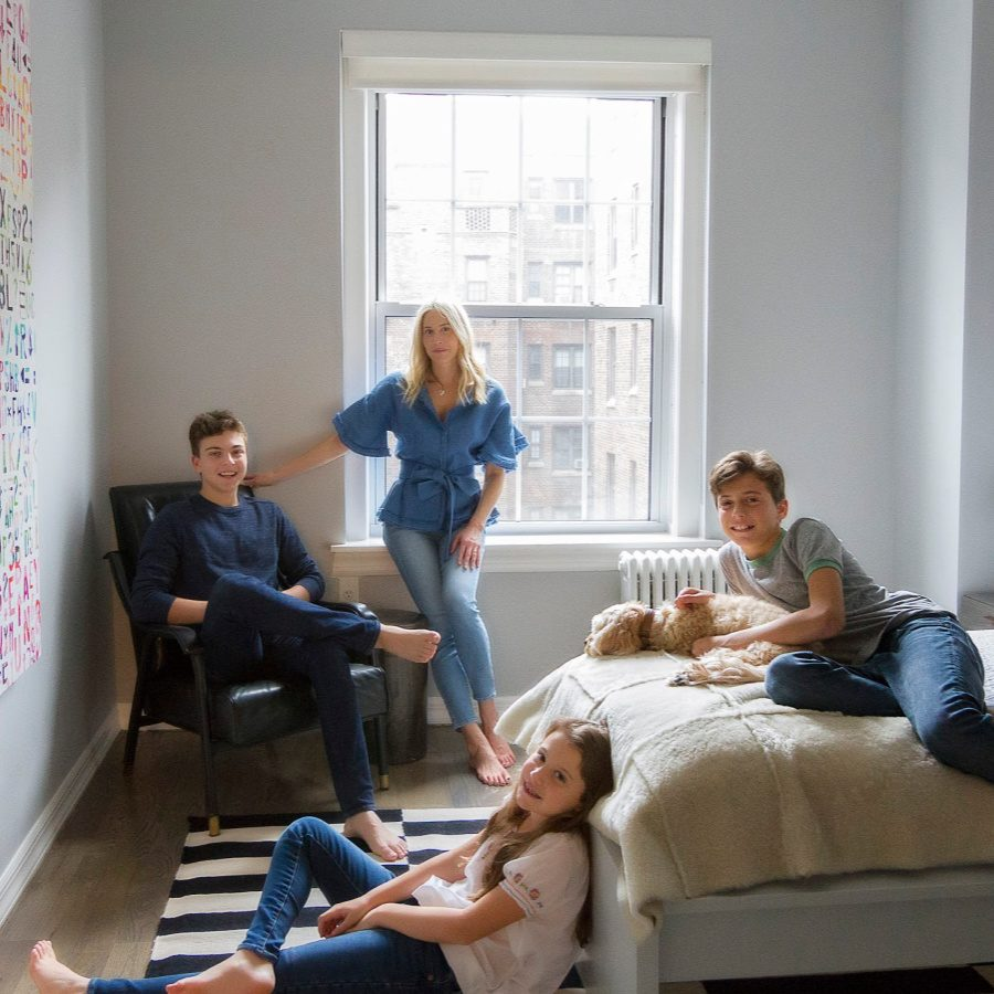 Lisa and her children relaxing in a room.
